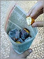 Venda ambulante de castanhas assadas embrulhadas em páginas de listas telefónicas