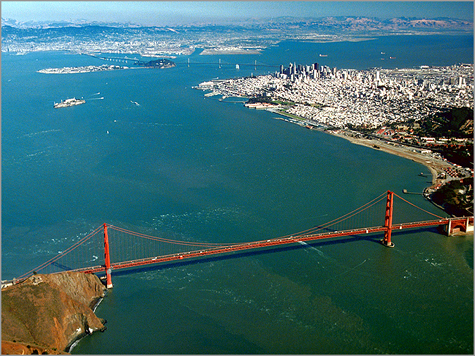 Vista aérea da Baía de San Francisco. Em primeiro plano, a Golden Gate Bridge; ao longe, os arranha-céus de Downtown; à esquerda, a famosa ilha de Alcatraz, assim chamada pelos espanhóis por nela haver muitos alcatraces (pelicanos)